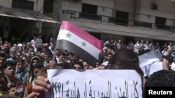 "Protesters hold a poster reading: ""All cities in Syria are terrorist!???"" during a demonstration in the port city of Banias."