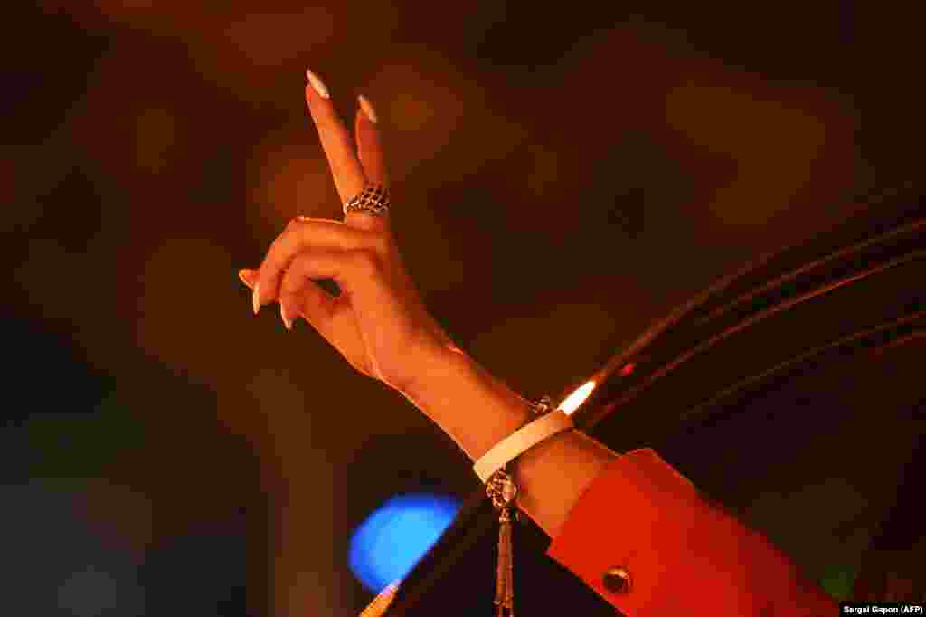A woman wearing a white bracelet, a symbol of the opposition, gestures from a car during a rally on the night of August 11.
