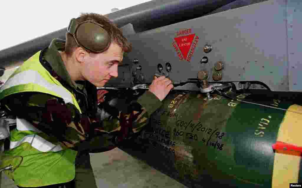 Një ushtar britanik duke kontrolluar raketat e një aeroplani Harrier GR7 në një bazë ushtarake në Itali, 27 mars 1999. Reuters.