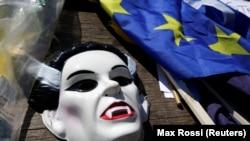 Britaniyanın Aİ-dən çıxmasına etirazlar səngimir. Fotoda etirazçı maskası və bayraq.