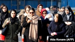 Iranian women wearing hijab walk down a street in the capital Tehran, February 7, 2018