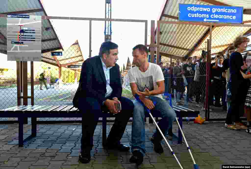 Former Georgian President Mikheil Saakashvili (left) sits on a bench after he got off the train to Lviv on the platform in Przemysl, Poland, on September 10 during his attempt to enter Ukraine despite official warnings. (epa-EFE/Darek Delmanowicz)