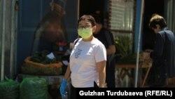 Женщина в маске и перчатках на рынке в Бишкеке. Иллюстративное фото.