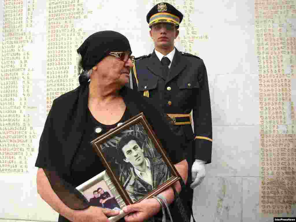 A woman holds portraits of her late son as she mourns at a memorial for victims of the Georgia-Abkhazia war during a ceremony on the anniversary of the conflict in Tbilisi.