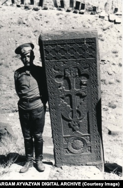 A soldier poses next to a Julfa khachkar in 1915.