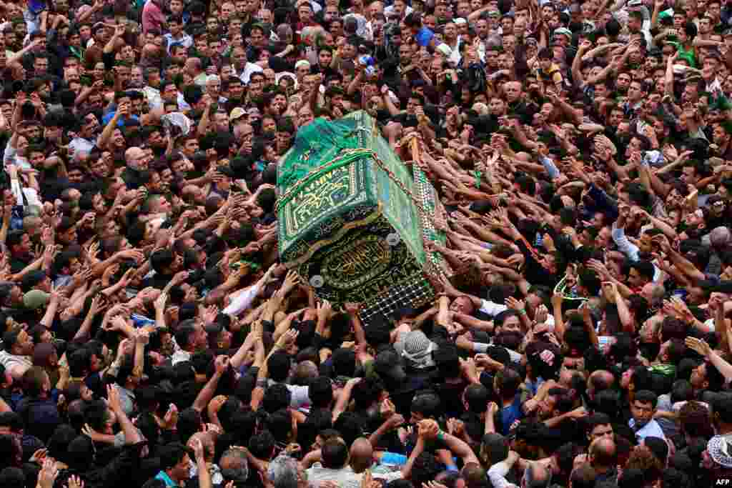 Iraqi Shi'ite Muslim worshippers carry the symbolic coffin of the 8th-century Imam Musa al-Kadhim during a funeral procession on the anniversary of his death at his shrine in Baghdad's northern district of Kadhimiya. (AFP/Sabah Arar)