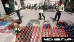Iranian police prepare to destroy confiscated bottles of alcohol in Tehran. File photo