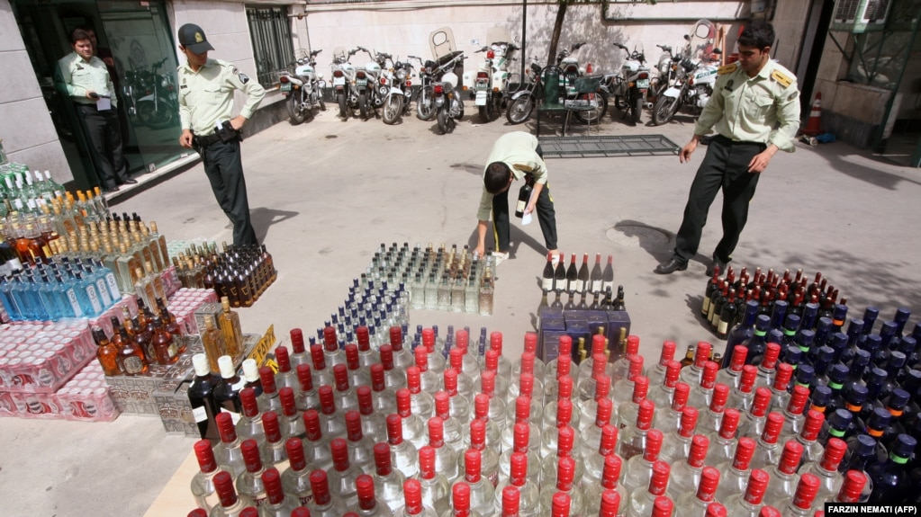 Iranian police prepare to destroy confiscated bottles of alcohol in Tehran.