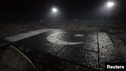 Students stand together to form the world's largest human flag to qualify for the Guinness World Records at the National Hockey Stadium in Lahore on October 22.