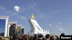 People gather as the statue is unveiled in Turkmenistan's capital, Ashgabat.
