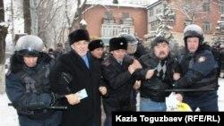 Полиция Хасен Қожахмет (сол жақта екінші) пен бірнеше адамды ұстап әкетті. Алматы, 17 желтоқсан 2011 ж.