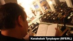 Мужчина держит в руке религиозную книгу на фоне проходящего богослужения. Иллюстративное фото.