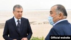 Өзбекстан президенті Шавкат Мирзияев (сол жақта) пен сенатор Әбдуғани Сангинов Сардоба су қоймасы жарылғаннан кейін су басқан аймақта тұр.