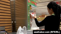 Ашғабаттағы супермаркетте ұн өлшеп салып тұрған әйел.