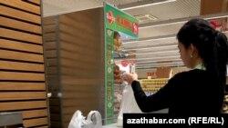 Девушка в супермаркете в Ашгабате расфасовывает муку для продажи.