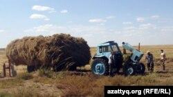 Ауыл адамдары Қазихан Баймұқашевтың бұзылған тракторын қарап жүр. Ақтөбе облысы, 8 қыркүйек 2012 жыл.