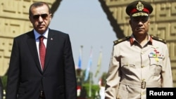Turkish Prime Minister Recep Tayyip Erdogan (left) pays a visit to the tomb of the late former President Anwar al-Sadat's in Cairo with Egyptian army commander General Hassan al-Roweny.
