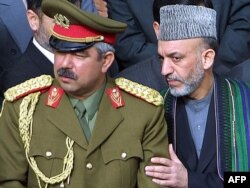 Ауғанстан президенті Хамид Карзай (оң жақта) қорғаныс министрінің орынбасары, генерал Абдул Рашид Дустумның жанында тұр. Мазари-Шариф, 21 наурыз 2002 жыл. (Көрнекі сурет)
