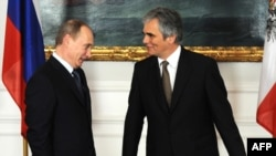 Russian Prime Minister Vladimir Putin (left) is welcomed by Austrian Chancellor Werner Faymann before their meeting in Vienna.