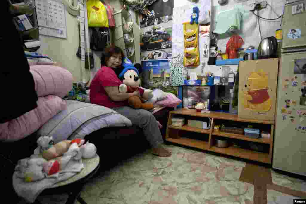 Lee Oi Lin, a 56-year-old woman, poses in her 4.1-square-meter subdivided flat inside an industrial building in Hong Kong. (2012 photo)