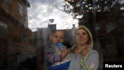 A Syrian refugee woman holds her son as she stands at the window of their friend's house at the Syrian-Turkish border town of Ceylanpinar in Syria.