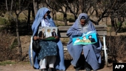 Two women hold posters of presidential candidate and former Islamist warlord Abdul Rasul Sayyaf in the western Herat Province. Women are expected to play a larger role in this election.