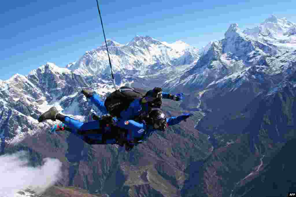 French multiple sclerosis sufferer Marc Kopp (bottom) freefalls with a tandem skydive partner over Nepal's Mount Everest region in a promotional photo for a company that claims the jump was the first by a disabled person over the area. (AFP Photo/Everest Skydive/Ryan Jackson)