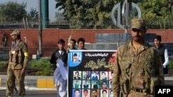 FILE: Pakistani students carry a banner bearing images of victims of the Peshawar school massacre.