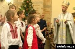 Діти біля чоловіка в образі святого Миколая під час урочистого відкриття святкової програми для дітей «Чудеса від святого Миколая». Київ, 16 грудня 2016 року