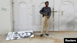 A policeman guards the sealed MQM party headquarters, where a poster depicting exiled party leader Altaf Hussain was torn down.