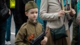 A young participant carries a toy gun in Sevastopol, Crimea, during the Immortal Regiment march on Victory Day, observed on May 9.