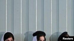دختران مدرسه ای در حال گوش فرا دادن به سخنرانی حامد کرزای، رییس جمهور افغانستان