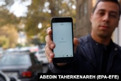 An Iranian man shows his phone while unable to load a social media page as internet service is reportedly disrupted, Tehran, Iran, 17 November 2019.