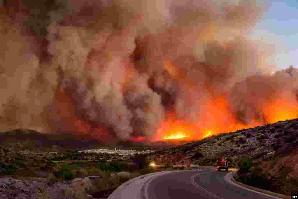 Shtëllunga tymi ngrihen mbi fshatin Lithium pasi flakët kapluan ishullin e Kios në Greqi, më 25 korrik.