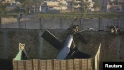 Part of the damaged U.S. helicopter is seen lying near the compound where Al-Qaeda leader Osama bin Laden was killed in Abbottabad in early May.