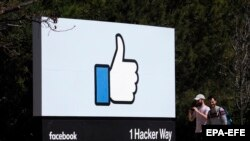 U.S. ECONOMY FACEBOOK RESULTS -- People walks past Facebook's 'Like' icon signage in front of their campus building in Menlo Park, California, U.S., 30 March 2018 (reissued 26 July 2018).