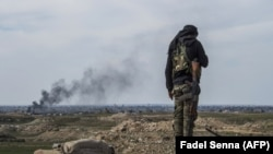 A fighter with the U.S.-backed Syrian Democratic Forces (SDF) keeps position during an operation to expel Islamic State group (IS) jihadists from the Baghouz area in the eastern Syrian province of Deir Ezzor, February 13, 2019