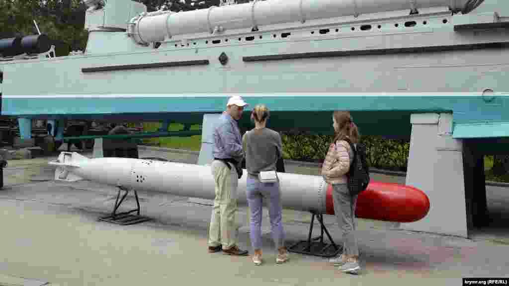 Відвідувачі розглядають військову техніку і озброєння –бронекатер і торпеду