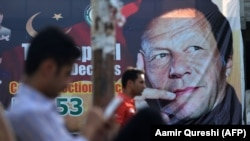 Pakistani men sit near a poster of Pakistan's cricketer-turned-politician and head of the Pakistan Tehreek-e Insaf (Movement for Justice) party Imran Khan, in Islamabad on July 30.