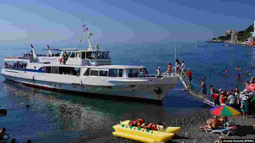 Всі охочі вирушити на морську прогулянку в Судак піднімаються на борт