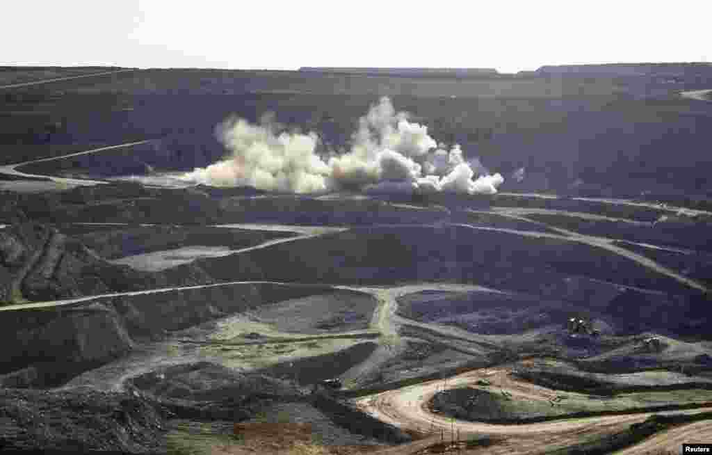 Controlled explosions raise dust at the open pit gold mine.