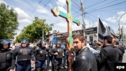 An Orthodox believer with a cross takes part in a protest against a rally organized by the LGBT community for human rights and equality in Chisinau on May 21.