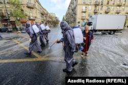 Muncitori care dezinfectează străzile din Baku, Azerbaidjan, drept măsură de prevenire a răspândirii pandemiei de coronavirus, 18 aprilie.