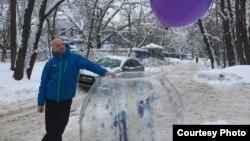 """Акционист Виктор Пашин рядом с большим надувным шаром, с которым он проводил перформанс """"Надувательство"""". Москва, 18 февраля 2018 года."""