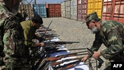 Afghan Army officers inspect weapons collected from private security companies in Kabul earlier this month.