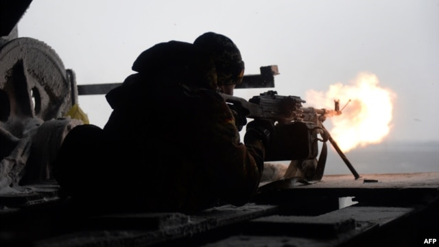 A Ukrainian Right Sector batallion volunteer fires a machine gun from his position near the eastern Ukrainian village of Pisky, in the Donetsk region, on January 3.