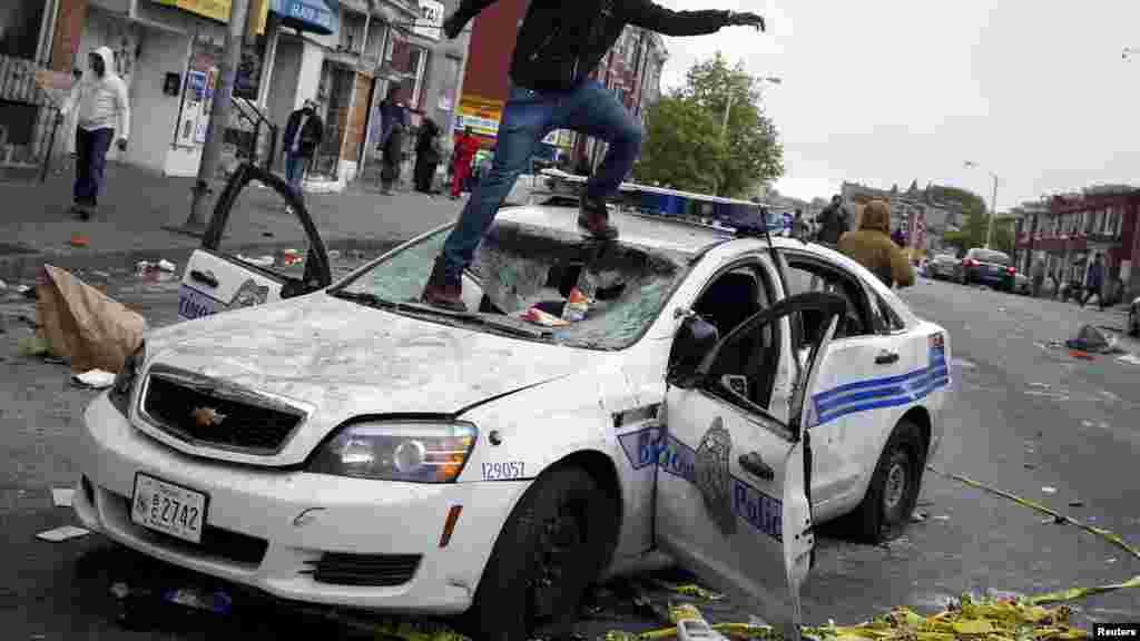 Один из участников уличных беспорядков в Балтиморе на поврежденной полицейской машине