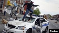 Baltimor-da dağıdılmış polis maşının üstünə çıxan aksiyaçı. 27 aprel 2015