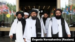 FILE: Members of a Taliban delegation, led by chief negotiator Mullah Abdul Ghani Baradar (Center, front), leave after peace talks with Afghan politicians in Moscow in May.