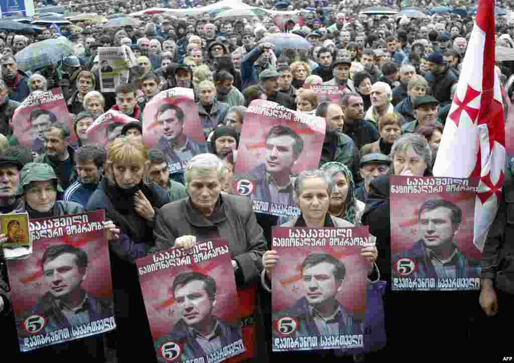Georgian opposition supporters hold portraits of opposition leader Mikheil Saakashvili during a rally outside the parliament in Tbilisi on November 10, 2003.